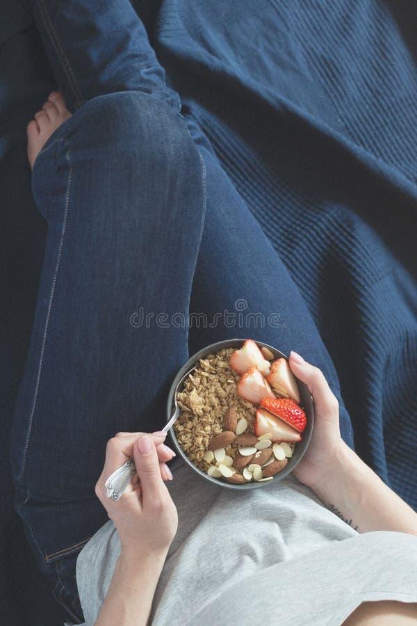 Cuenco de cerámica gris del desayuno sano con el granola, la fresa y las nueces en manos del ` s de la mujer Dieta y concepto de  fotografía de archivo libre de regalías
