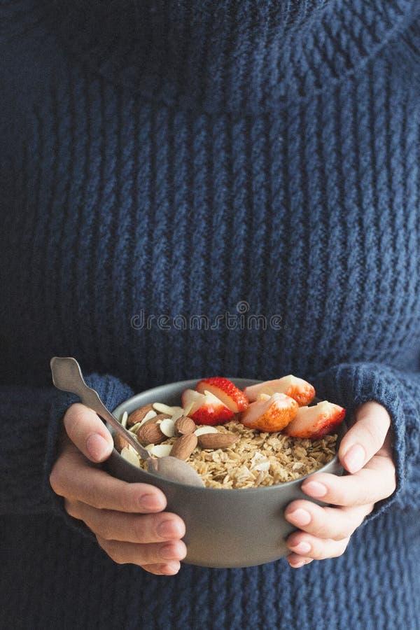 Cuenco de cerámica gris del desayuno sano con el granola, la fresa y las nueces en manos del ` s de la mujer Dieta y concepto de  imágenes de archivo libres de regalías