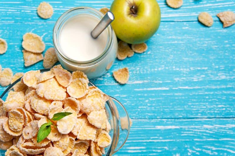 Cuenco de cereal de los copos de maíz en una tabla de madera azul y una manzana fresca, leche detrás fotografía de archivo
