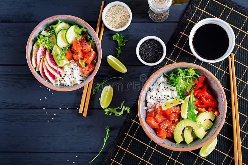 Cuenco de color salmón hawaiano del empuje de los pescados con arroz, el aguacate, la paprika, el pepino, el rábano, las semillas imagen de archivo libre de regalías