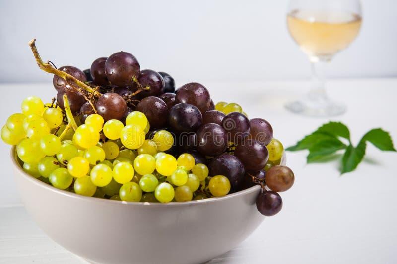 Cuenco de diversas uvas: bayas rojas, blancas y negras en la tabla de madera blanca con el vidrio del vino blanco y de la hoja ve imagen de archivo libre de regalías