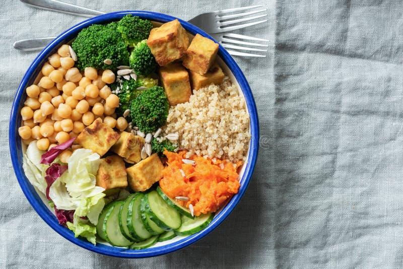 Cuenco de ensalada con la quinoa, el queso de soja, los garbanzos y las verduras imágenes de archivo libres de regalías