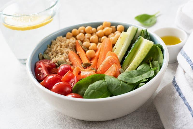 Cuenco de ensalada con la quinoa, los garbanzos, el pepino, las zanahorias de bebé, la espinaca y los tomates imagenes de archivo