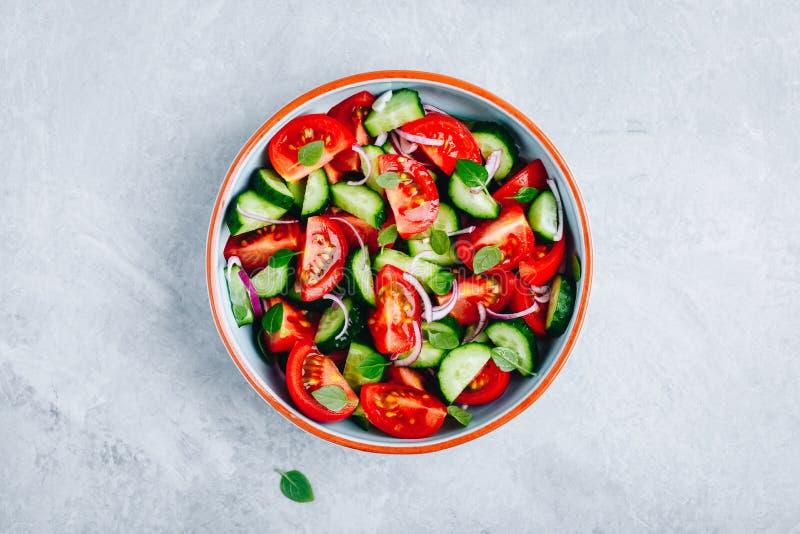 Cuenco de ensalada fresco del verano con los tomates, los pepinos, las cebollas rojas, la albahaca y la preparaci?n del aceite de imagenes de archivo