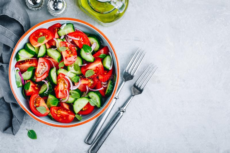 Cuenco de ensalada fresco del verano con los tomates, los pepinos, las cebollas rojas, la albahaca y la preparaci?n del aceite de imágenes de archivo libres de regalías