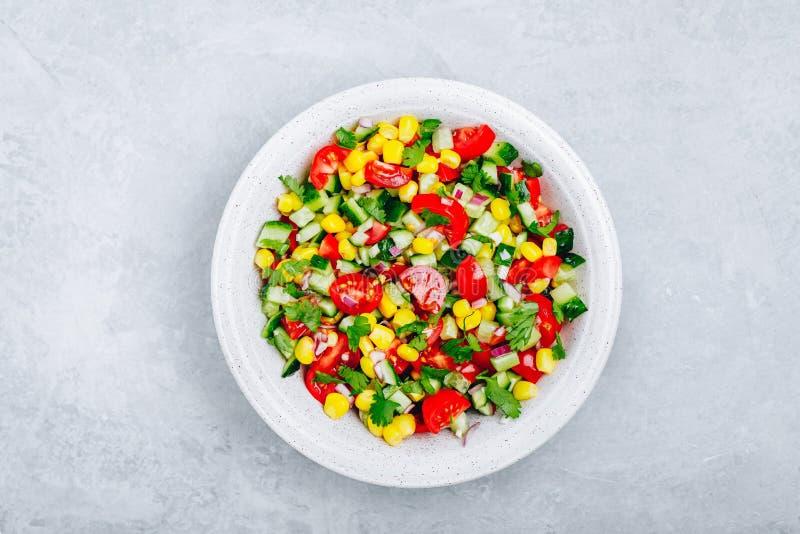 Cuenco de ensalada fresco de maíz del verano con los tomates, los pepinos, las cebollas rojas y el perejil imágenes de archivo libres de regalías