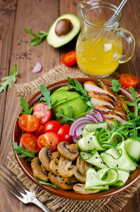 Cuenco de ensalada sano con el pollo, las setas, los tomates, los pepinos, el aguacate y el arugula fotografía de archivo