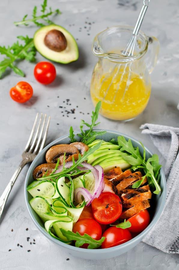 Cuenco de ensalada sano con el pollo, las setas, los tomates, los pepinos, el aguacate y el arugula imágenes de archivo libres de regalías