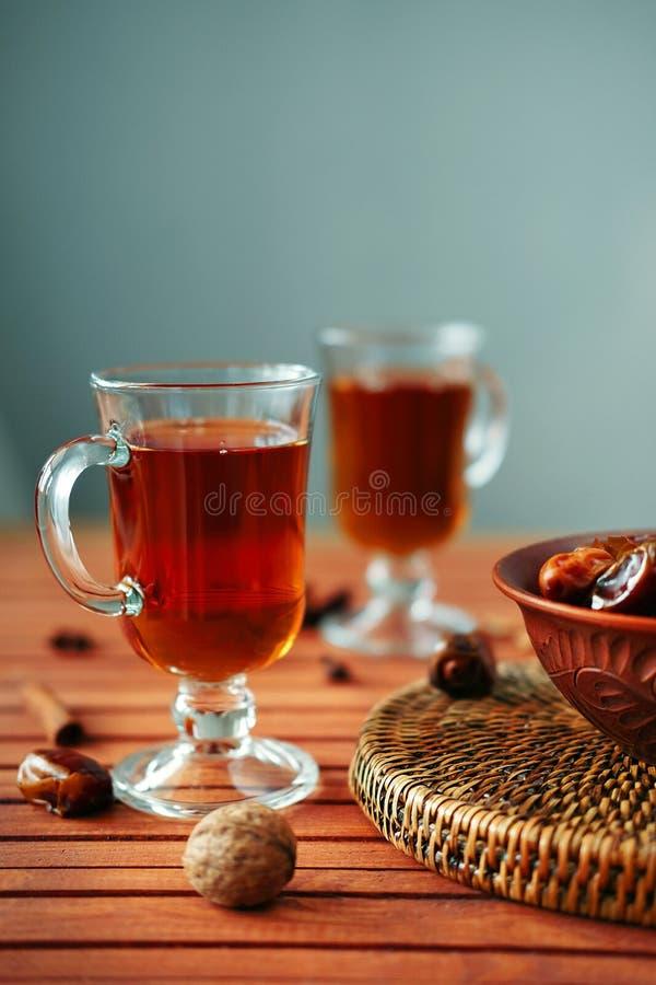 Cuenco de fechas secadas en la tabla de madera vieja con té foto de archivo libre de regalías