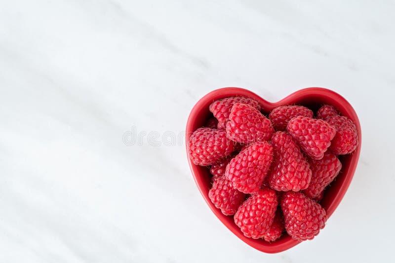 Cuenco de frambuesas rojas frescas para el postre, cuenco de cerámica en forma de corazón rojo, fondo de mármol blanco imagen de archivo libre de regalías