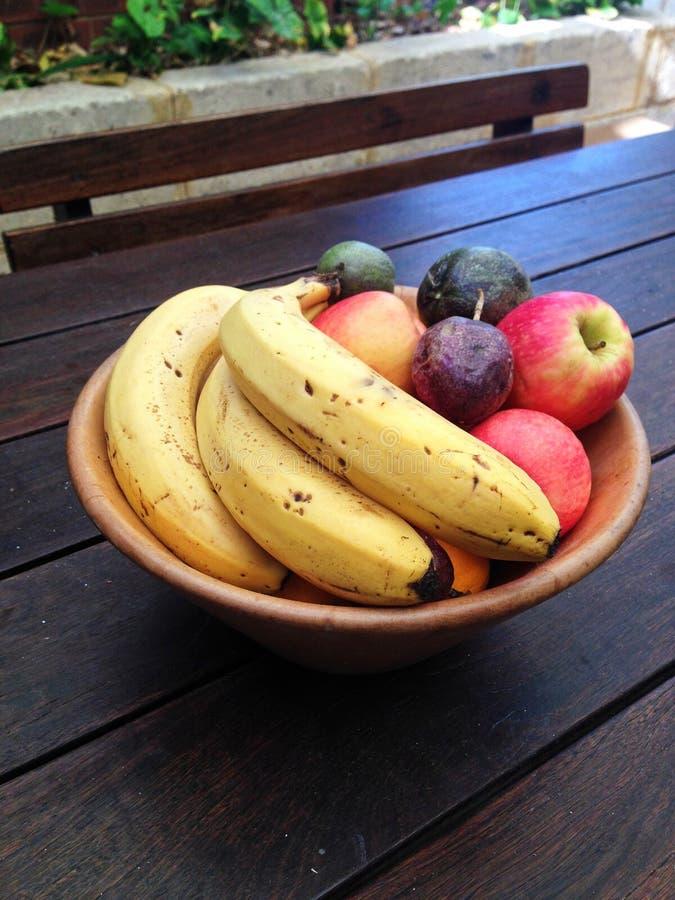 Cuenco de fruta incluyendo plátanos, manzanas y fruta de la pasión en una tabla de madera al aire libre imagen de archivo