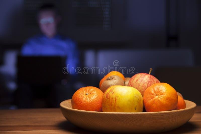 Cuenco de frutas en una mesa y hombre trabajando con laptop imagen de archivo
