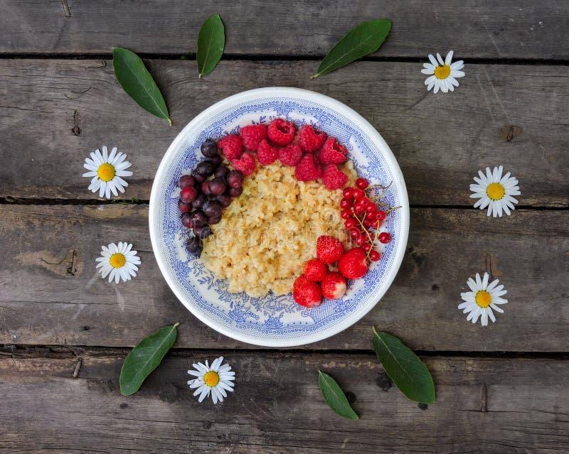 Cuenco de gachas de avena de la harina de avena con las fresas y las frambuesas frescas Endecha plana del desayuno sano, visión s imágenes de archivo libres de regalías