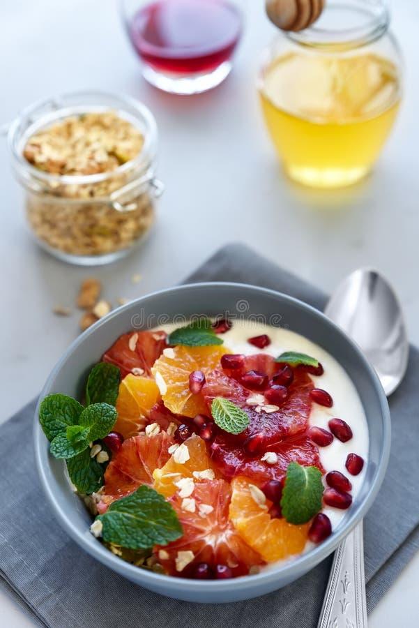 Cuenco de granola hecho en casa con el yogur, semillas de la fruta cítrica y de la granada en fondo de madera gris Foco selectivo fotografía de archivo