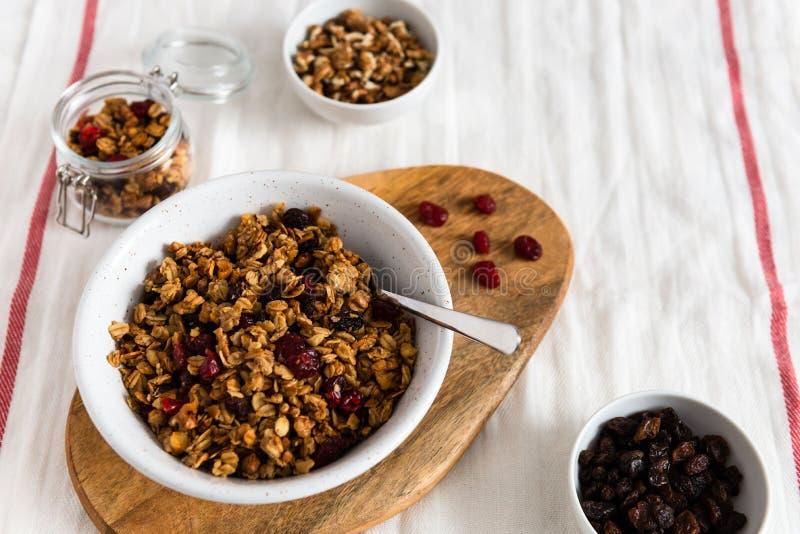 Cuenco de granola hecho en casa con las nueces y las frutas en el fondo de lino blanco Vista lateral, espacio de la copia concept fotos de archivo