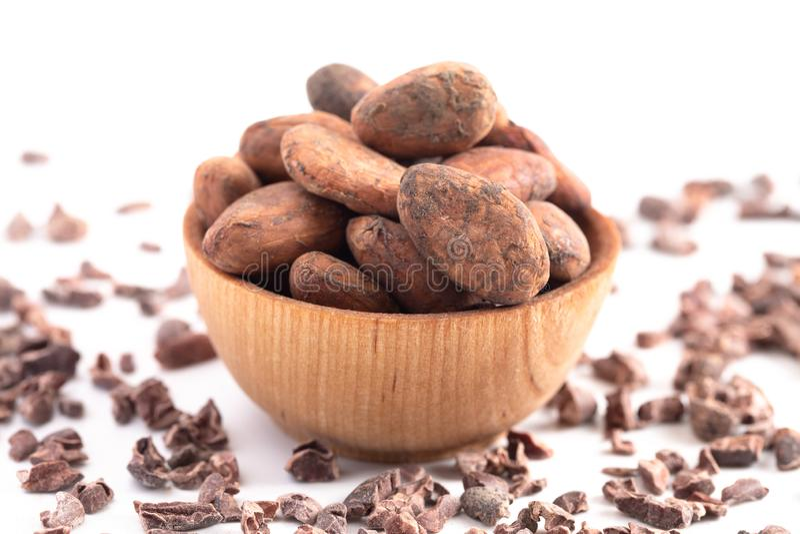 Cuenco de granos de cacao crudos y de semillas del chocolate aislados en un fondo blanco imagen de archivo