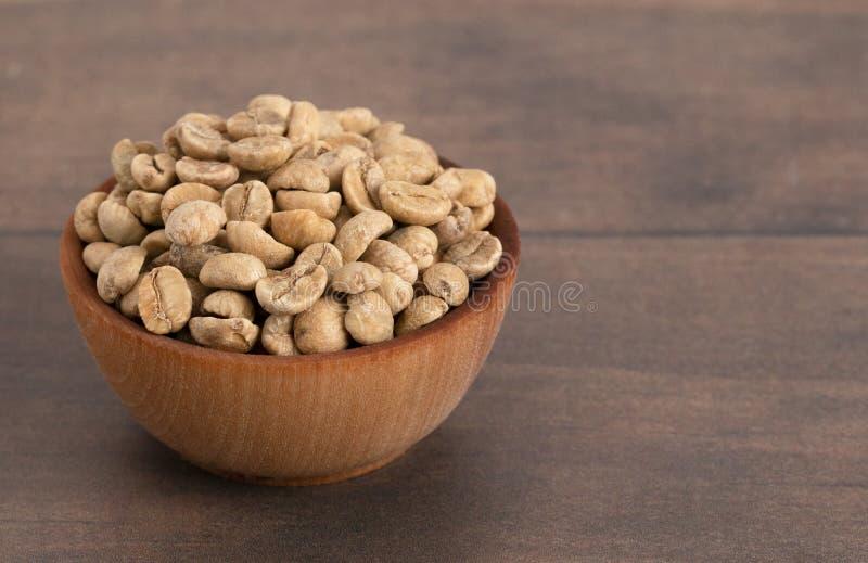 Cuenco de granos de café verdes crudos en una tabla de madera imagen de archivo