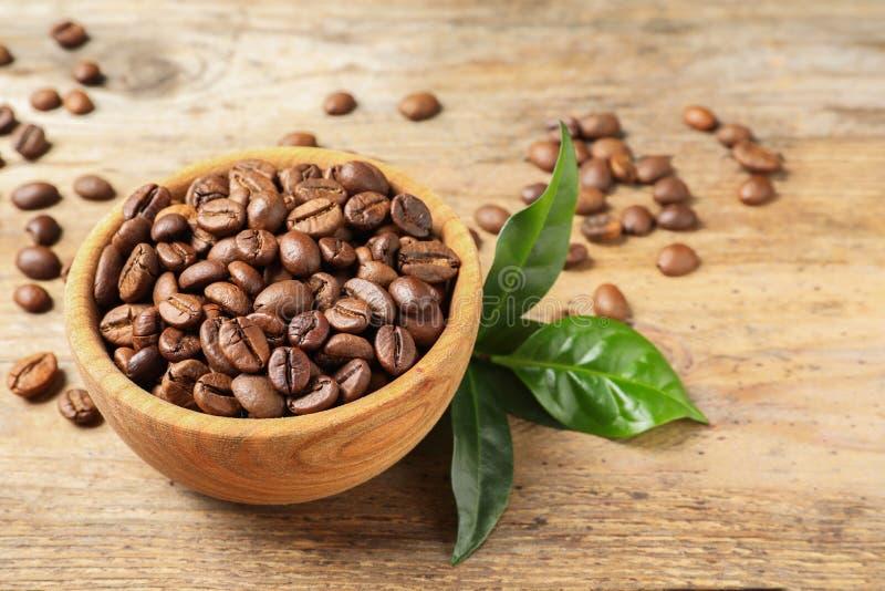 Cuenco de granos de café y de hojas verdes frescas en la tabla de madera fotografía de archivo libre de regalías