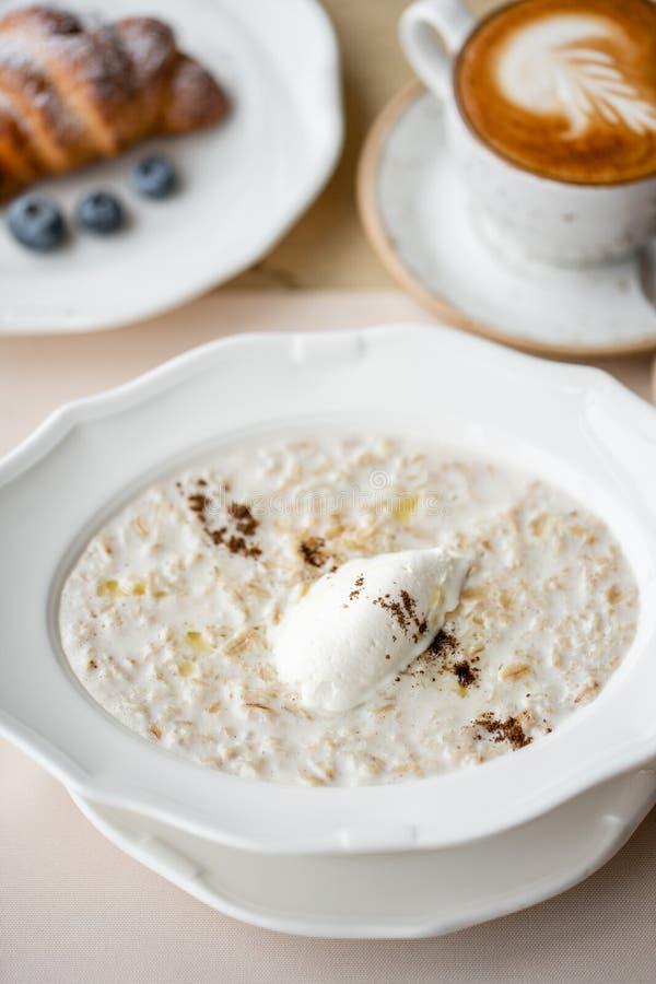 Cuenco de harina de avena del desayuno con queso y canela italianos suaves Cruasanes, caf? y otros platos en la tabla en imágenes de archivo libres de regalías