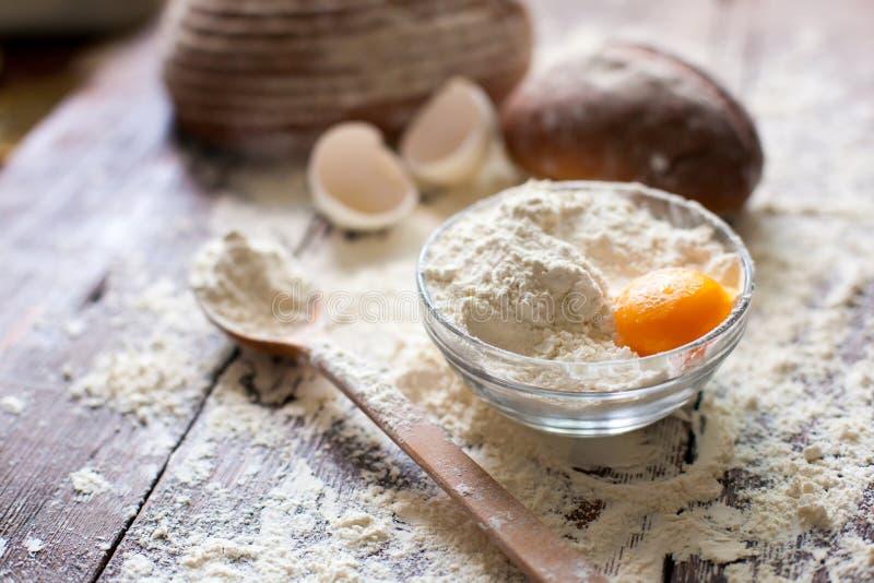 Cuenco de harina con el huevo y el pan fotografía de archivo