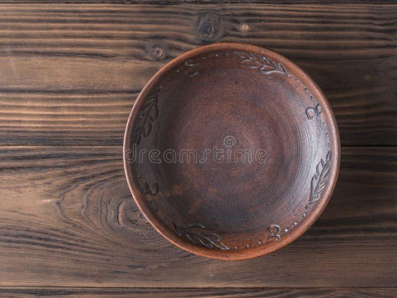 Cuenco de la arcilla en una tabla de madera marrón La visi?n desde la tapa Cer?mica para la cocina imagenes de archivo