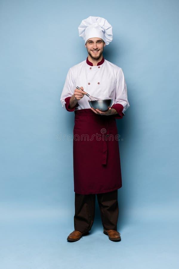 Cuenco de la tenencia del cocinero y batidor sonrientes del alambre en fondo azul Cocinero que hace la comida imagenes de archivo