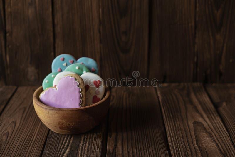 Cuenco de madera con el pan de jengibre glased hecho en casa en forma de corazón fotos de archivo libres de regalías