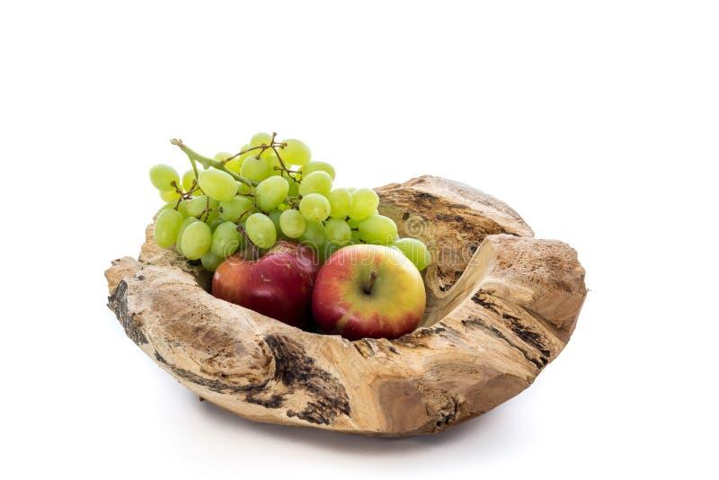 Cuenco de madera con las manzanas y un manojo de uvas fotografía de archivo libre de regalías