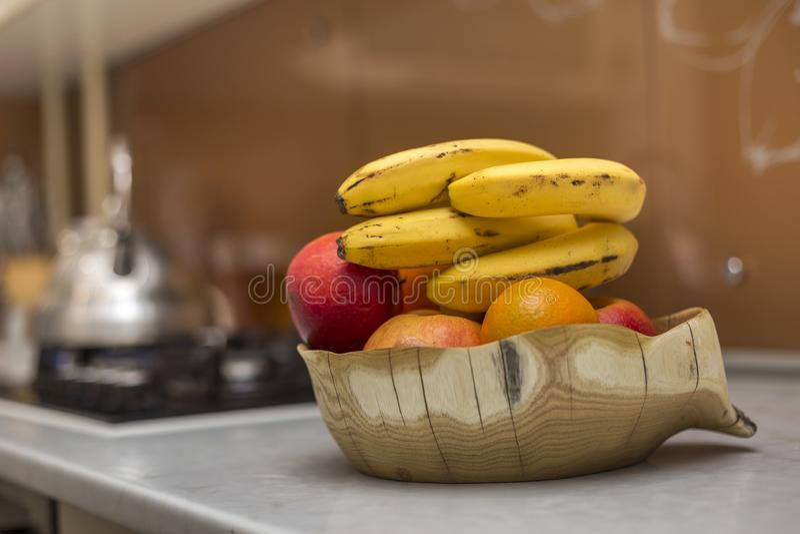 Cuenco de madera de la placa con las manzanas deliciosas deliciosas frescas de la fruta plátanos y naranja en la tabla de cocina  fotografía de archivo libre de regalías