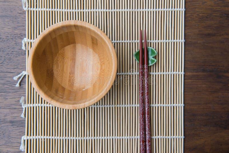 Cuenco de madera de la visión superior con los palillos en la estera de bambú en la tabla de madera imagen de archivo libre de regalías