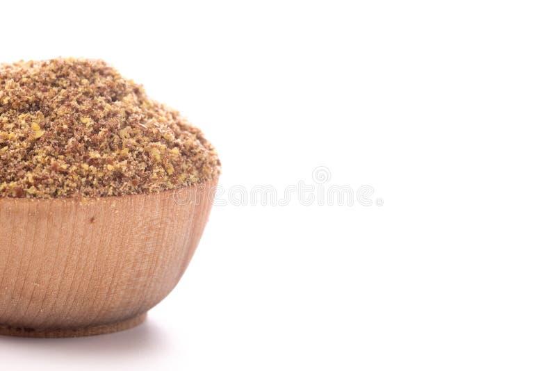 Cuenco de madera lleno de semillas de lino de tierra en un fondo blanco imagenes de archivo