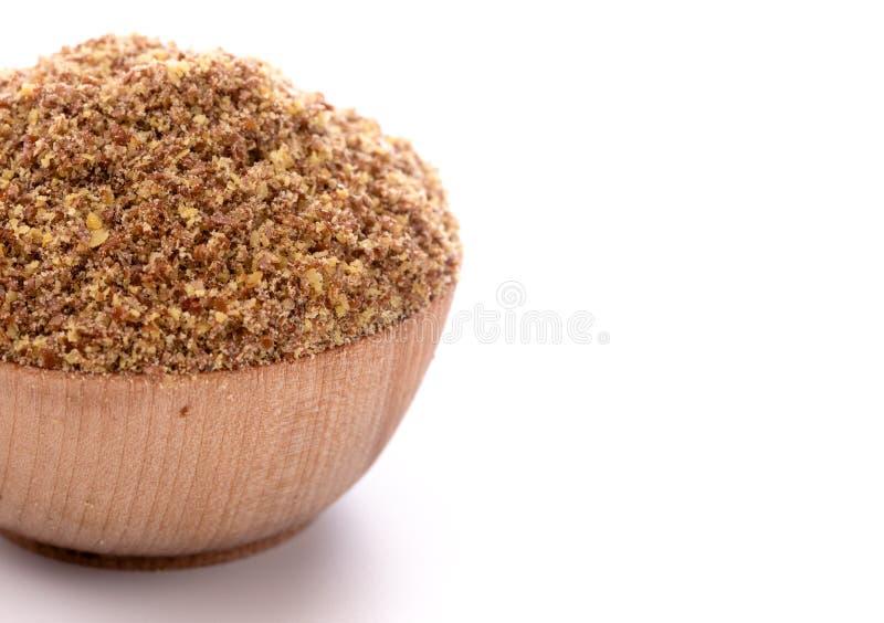Cuenco de madera lleno de semillas de lino de tierra en un fondo blanco imagen de archivo libre de regalías