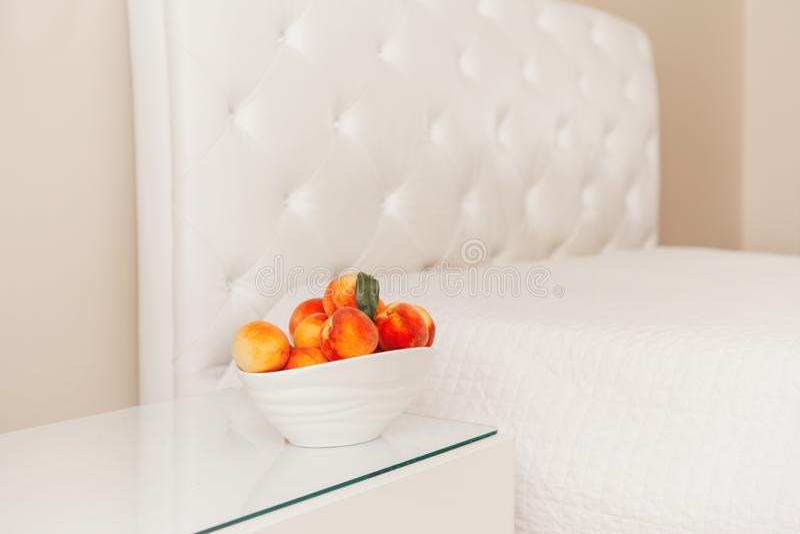 Cuenco de melocotones maduros dulces frescos de las frutas en la tabla cerca de la cama blanca vacía imagen de archivo