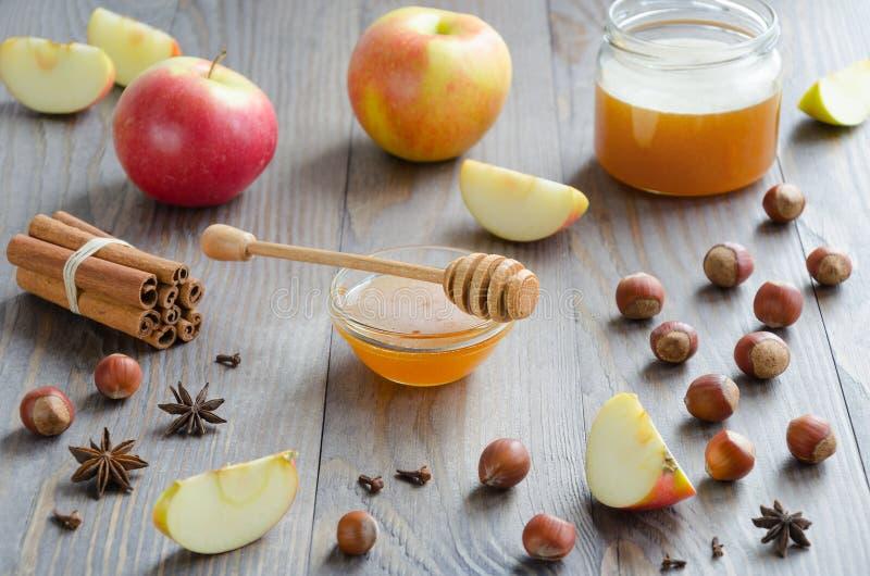 Cuenco de miel con el palillo, el canela, avellanas, manzanas y especias de la miel foto de archivo