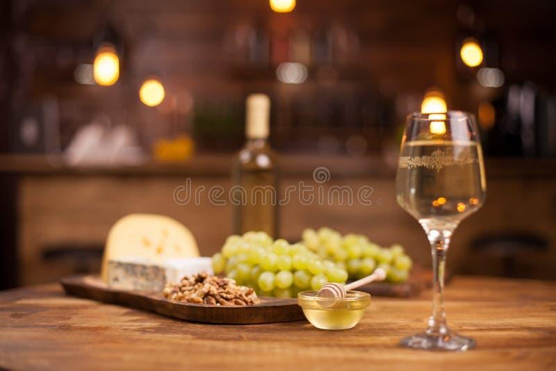 Cuenco de miel de oro deliciosa al lado de un vidrio de vino blanco fotografía de archivo