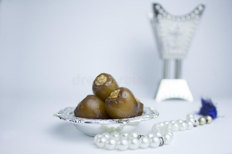 Cuenco de plata árabe elegante con las fechas, el perfume y la perla fotos de archivo