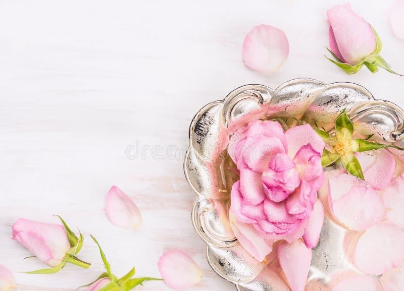 Cuenco de plata con las rosas y agua en el fondo de madera blanco imagen de archivo