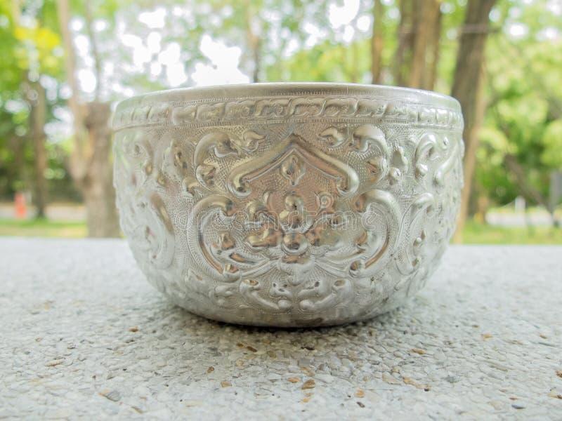 Cuenco de plata retro en la tierra de piedra imagen de archivo