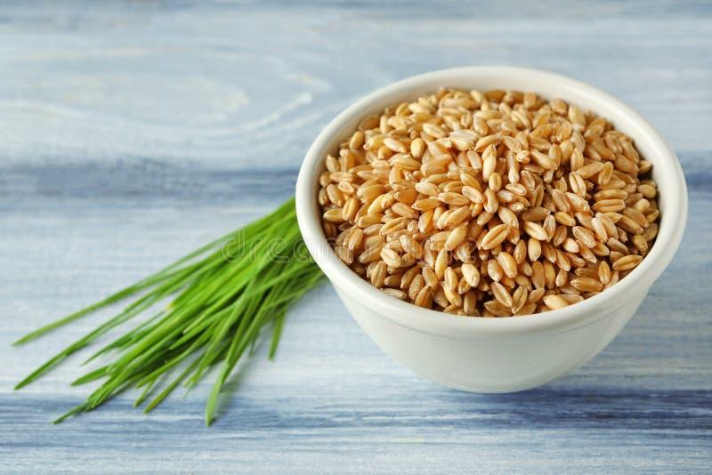 Cuenco de semillas y de brotes de la hierba del trigo en la tabla imagen de archivo libre de regalías