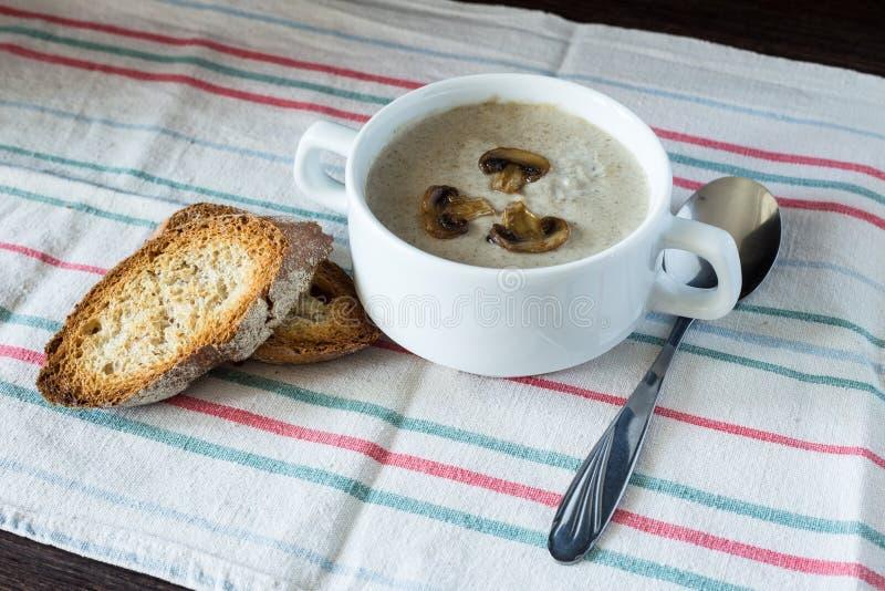 Cuenco de sopa de champiñones con pan en el tablero de madera fotos de archivo