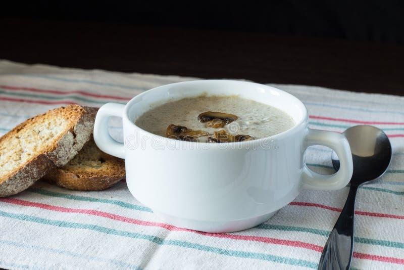 Cuenco de sopa de champiñones con pan en el tablero de madera imagenes de archivo