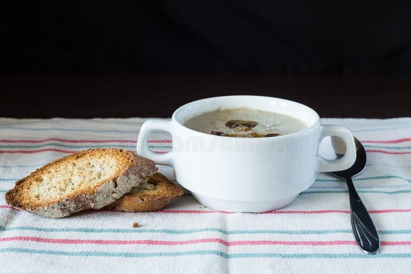 Cuenco de sopa de champiñones con pan en el tablero de madera fotos de archivo libres de regalías