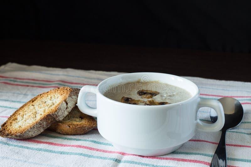 Cuenco de sopa de champiñones con pan en el tablero de madera fotografía de archivo libre de regalías