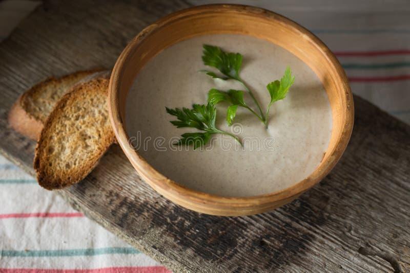 Cuenco de sopa de champiñones con pan en el tablero de madera imagen de archivo
