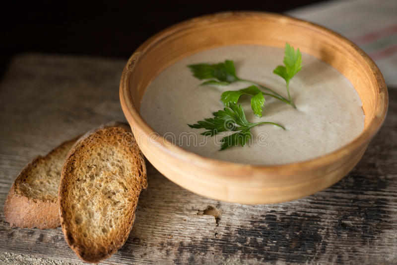 Cuenco de sopa de champiñones con pan en el tablero de madera imágenes de archivo libres de regalías