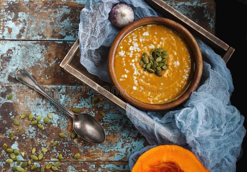 Cuenco de sopa hecha en casa tradicional de la calabaza con los seads, la crema y el pan en la tabla de madera rústica fotografía de archivo libre de regalías