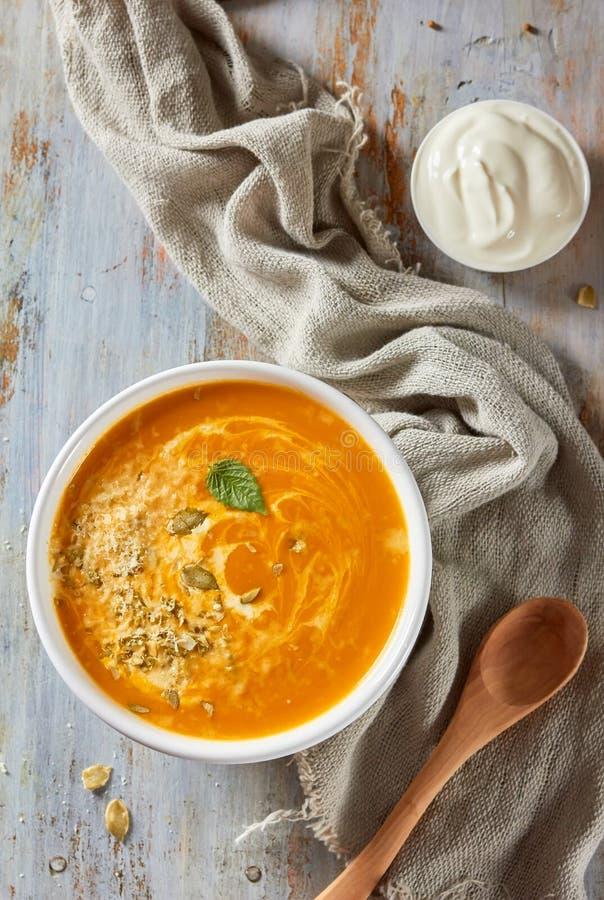 Cuenco de sopa de la calabaza con queso y crema fotos de archivo