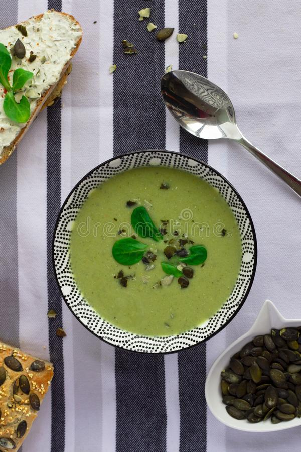 Cuenco de sopa de la crema del bróculi, de pan del grano con las semillas de calabaza y de cuchara en la tabla, concepto vegetari foto de archivo