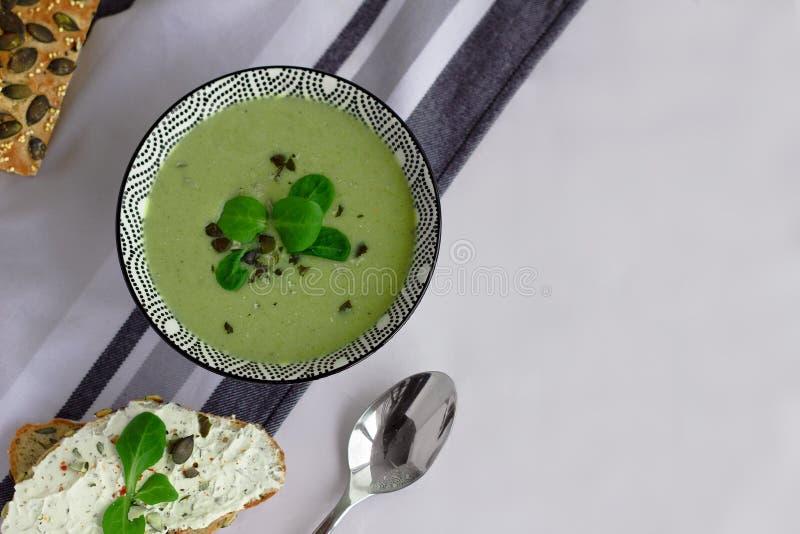 Cuenco de sopa de la crema del bróculi, de pan del grano con las semillas de calabaza y de cuchara en la tabla, concepto vegetari imagenes de archivo