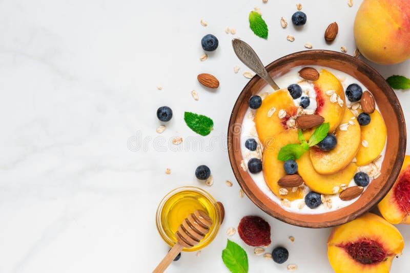 Cuenco de yogur griego con el melocotón, la avena, las nueces, la menta, la miel y los arándanos con una cuchara para la opinión  foto de archivo libre de regalías